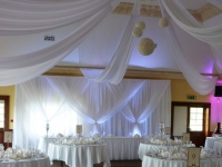 Grecian backdrop white uplighters and non swag front table